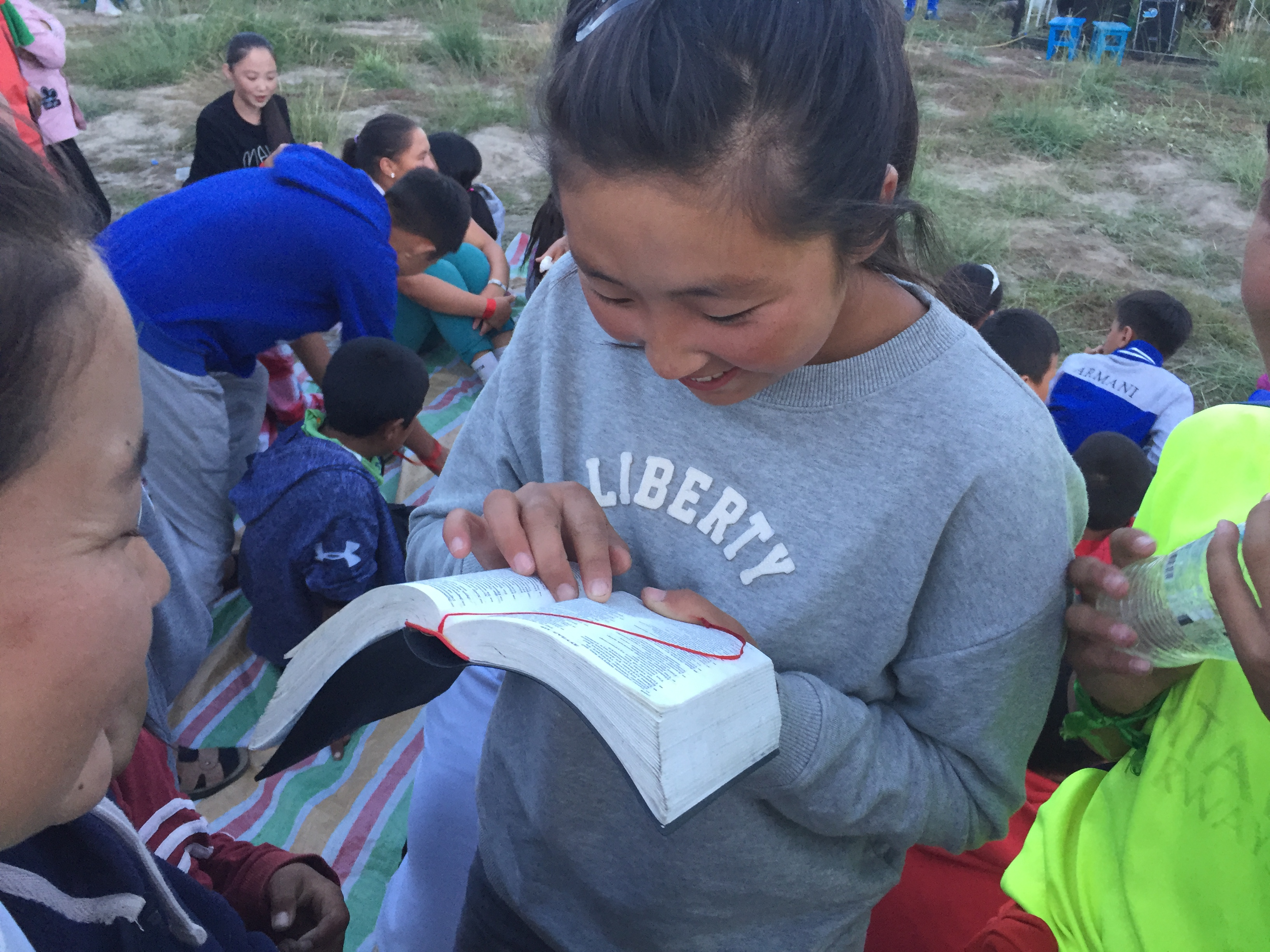 Young girl reading the Bible at a summer Bible camp in Mongolia