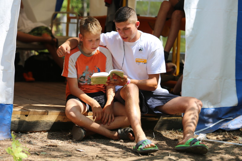 School Without Walls leader reading the New Testament with a child at summer Bible camp