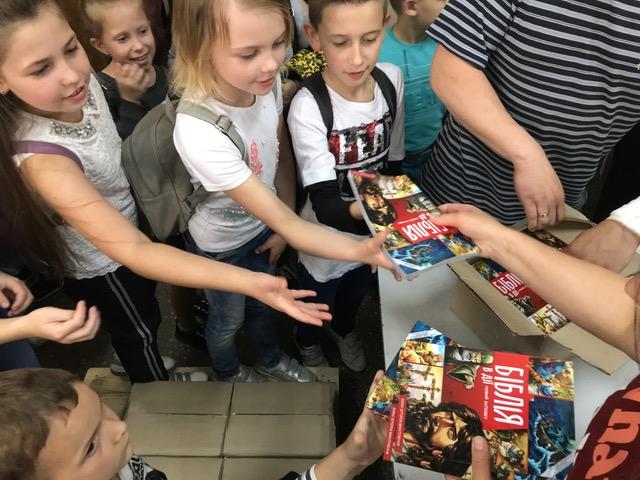 School-aged children in Ukraine receiving copies of the specially designed Action Bible New Testament